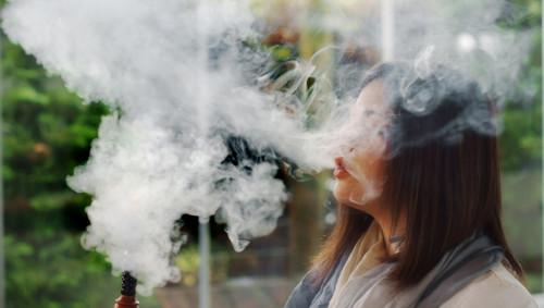 Eine junge Frau raucht Wasserpfeife und ist in eine Rauchwolke eingehüllt.