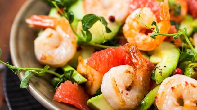 Man sieht einen Shrimpssalat mit Avocado und Gurke.