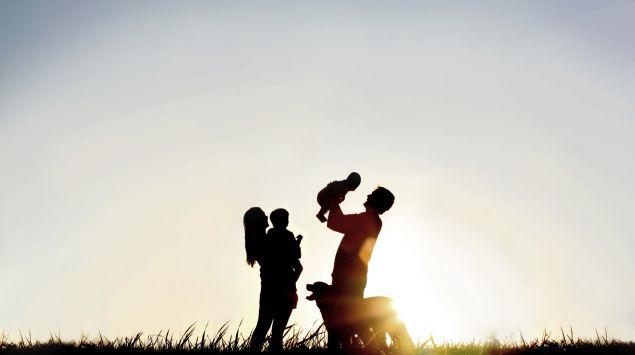 Das Bild zeigt eine Familie mit Hund bei Sonnenuntergang