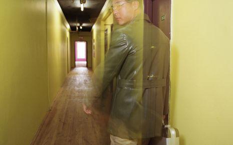 Ein nur halb transparent dargestellter Mann in einem Flur.