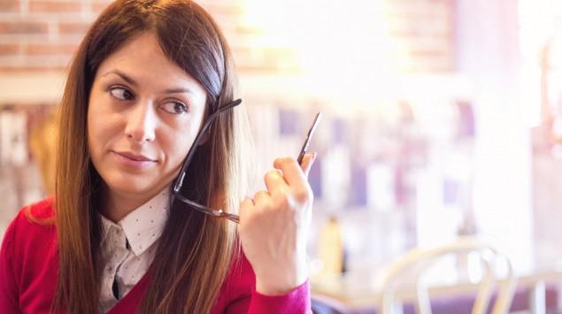 Eine skeptisch guckende Frau sitzt an einem Tisch und hält eine Brille in der linken Hand.
