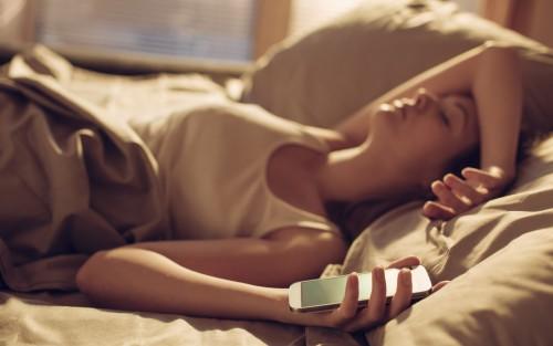 Schlafende Frau mit Smartphone in der Hand.