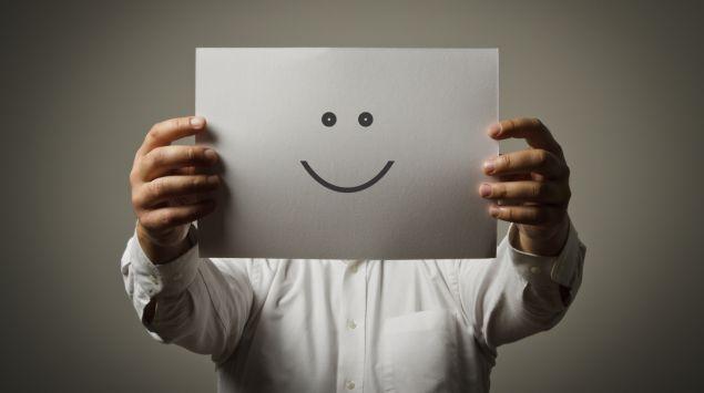 Ein Mann hält sich ein Blatt Papier mit einem aufgemalten Smiley vors Gesicht.