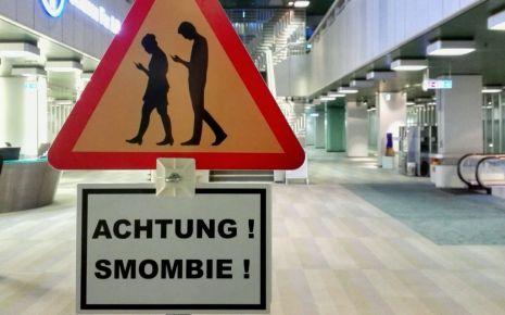 """Das Wort """"Smombie"""" (eine Mischung aus Smartphone und Zombie) wurde 2015 zum Jugendwort des Jahres gewählt. Gemeint sind damit Menschen, die durch den ständigen Blick auf ihr Smartphone so stark abgelenkt sind, dass sie ihre Umgebung kaum noch wahrnehmen."""