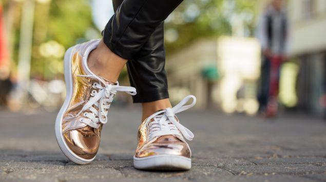 Füße einer Frau in goldenen Sneakern.
