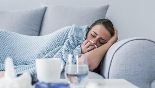 Eine junge Frau liegt unter einer Decke auf einem Sofa und putzt sich die Nase.