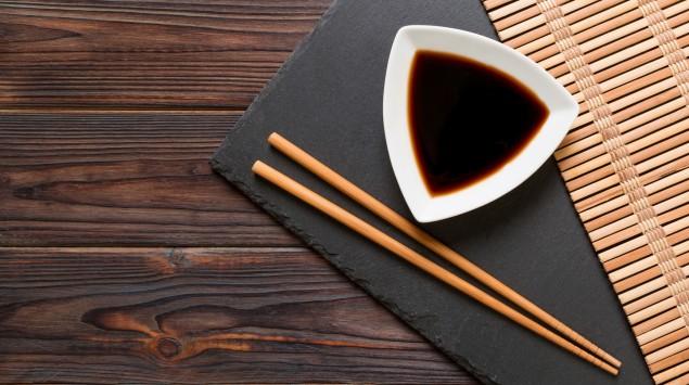 Auf einem braunen Holztisch liegt eine schwarze Servierplatte mit Bambusmatte, darauf ein Schälchen mit Sojasauce und Essstäbchen.