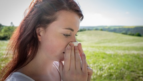 Eine Frau steht auf einer sommerlichen Wiese und putzt sich die Nase.