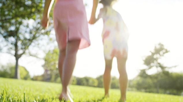 Man sieht unbekleidete Beine auf einer Wiese.