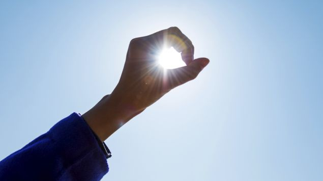 Das Bild zeigt eine Hand, durch die man die Sonne sieht.