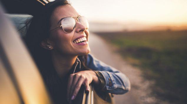 Eine Frau mit Sonnenbrille lacht aus einem Autofenster.
