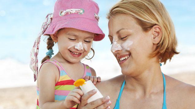Eine Frau und ein Mädchen reiben sich am Strand mit Sonnenmilch ein.