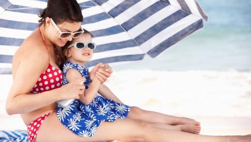 Eine Mutter cremt ihre Tochter mit Sonnenmilch ein.