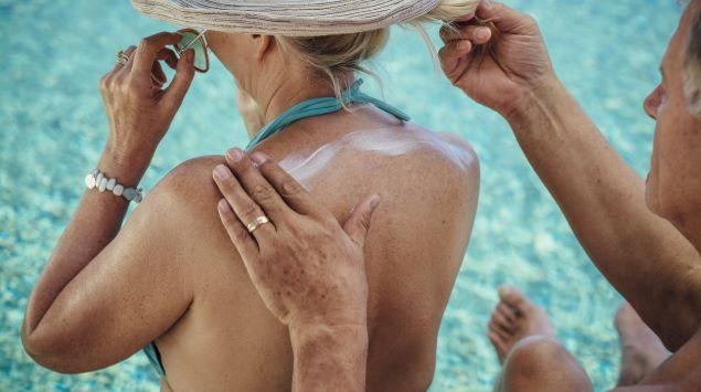 Ein Mann cremt eine Frau mit Sonnencreme ein.