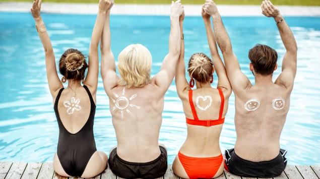 Man sieht vier Menschen von hinten, die am Beckenrand eines Schwimmbads sitzen und Sonnencreme auf dem Rücken haben.
