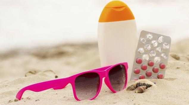 Sonnencreme, Sonnenbrille und Tabletten am Strand.