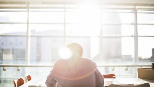 Das Bild zeigt einen Mann, der vor einem Fenster an einem großen Tisch sitzt.