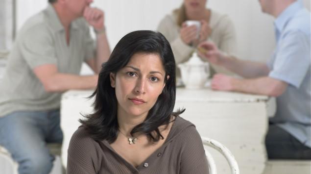 Das Bild zeigt eine traurige Frau und drei Personen, die im Hintergrund Karten spielen.
