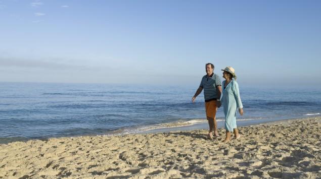 Das Bild zeigt ein Paar, das am Strand spazieren geht.