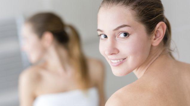Eine Frau steht vor dem Spiegel und blickt über ihre Schulter.