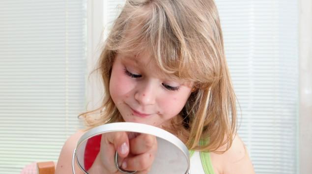 Das Bild zeigt ein Kind mit Windpocken, das in einen Handspiegel guckt.