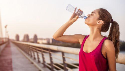 Das Bild zeigt eine sportliche Frau, die aus einer Wasserflasche trinkt.
