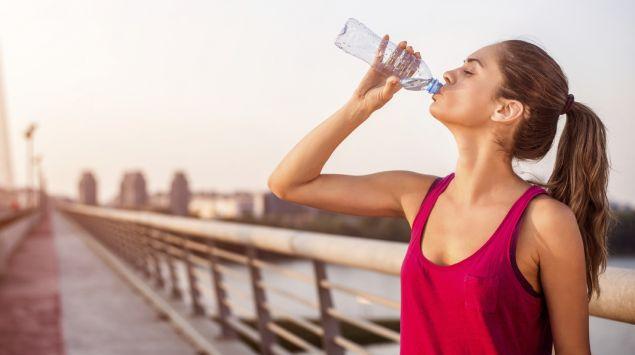 Mineralwasser kann zu Deckung des Magnesiumbedarfs beitragen. Eine Frau trinkt Wasser aus einer Flasche.