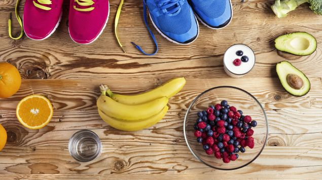 Das Bild zeigt zwei Paar Laufschuhe und verschiedene Früchte auf einem Holztisch.