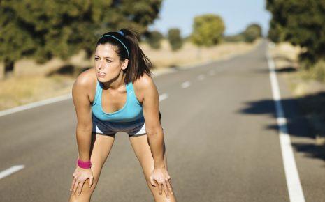 Das Bild zeigt eine erschöpfte Frau nach dem Sport.