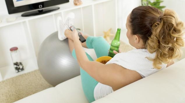 Eine Fraus sitzt in Sportklamotten auf dem Sofa und schaut sich Sportübungen im Fernsehen an.