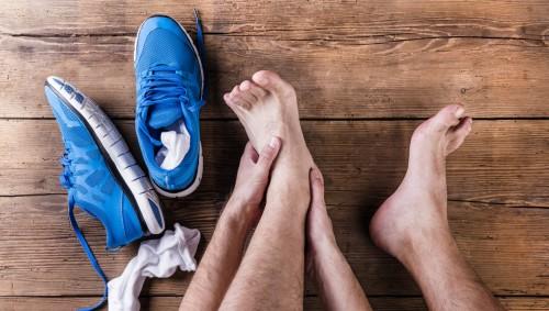 Ein Mann hat sich die Sportschuhe ausgezogen und hält sich den Fuß.