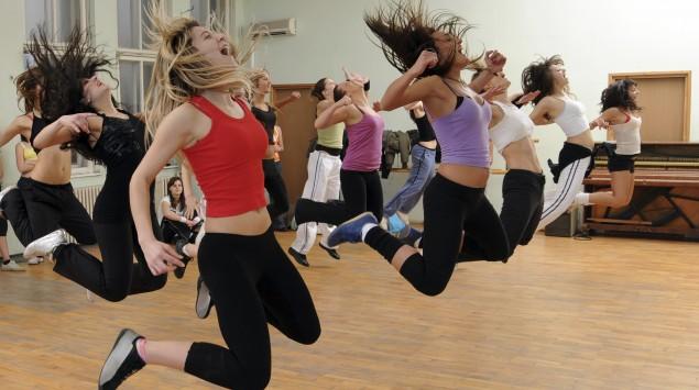 Das Bild zeigt Frauen, die einen Sportkurs machen und springen.