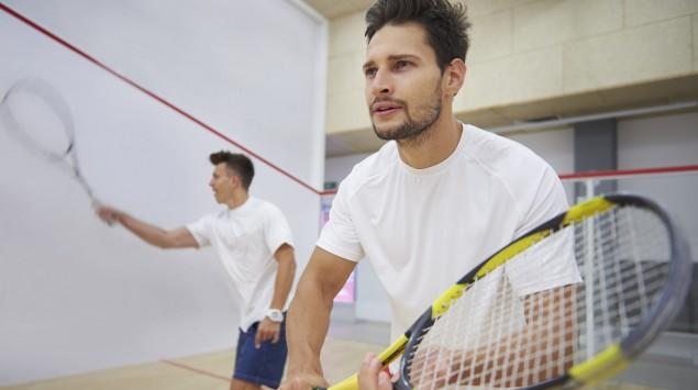 Zwei Männer spielen Squash.