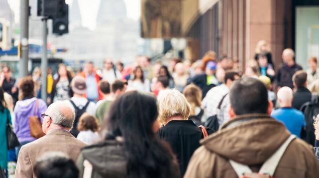 In einer Stadt sind viele Menschen zu Fuß unterwegs.