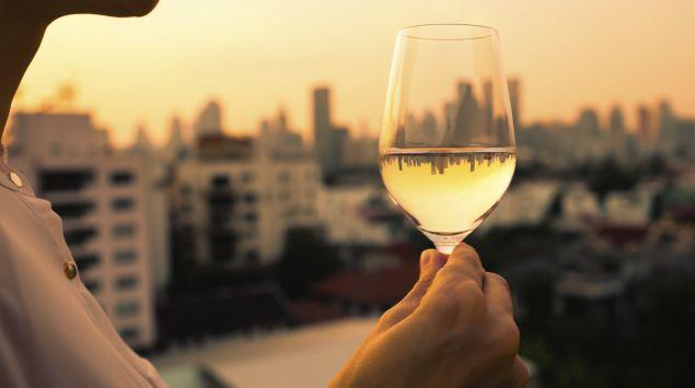 Eine Frau hält ein Glas Weißwein in der Hand, im Hintergrund sieht man eine eine Skyline im Abendlicht.