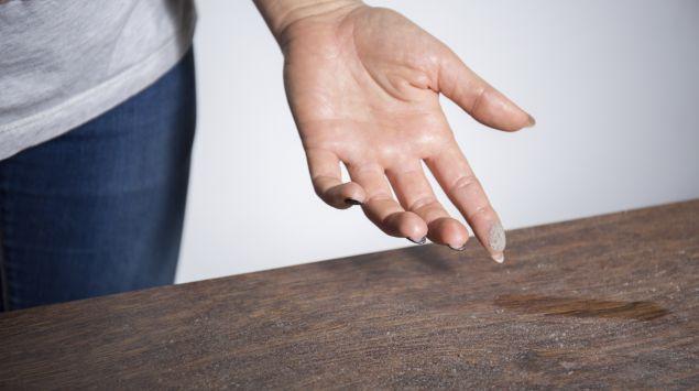 Eine Frau hat mit dem Finger über einen staubigen Tisch gewischt.