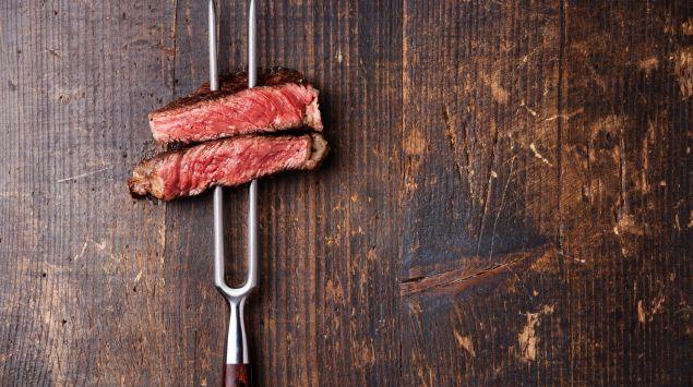 Auf einer Fleischgabel stecken zwei Stück Rindersteak