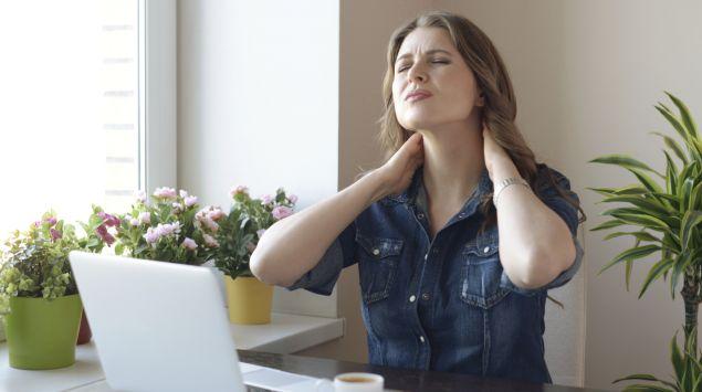 Eine Frau sitzt am Tisch und fasst sich an den schmerzenden Nacken.