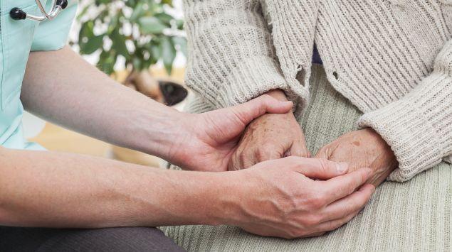 Man sieht eine Ärztin, die einer älteren Frau die Hand hält.
