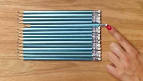 Eine Frau legt mehrere Bleistifte exakt parallel zueinander.