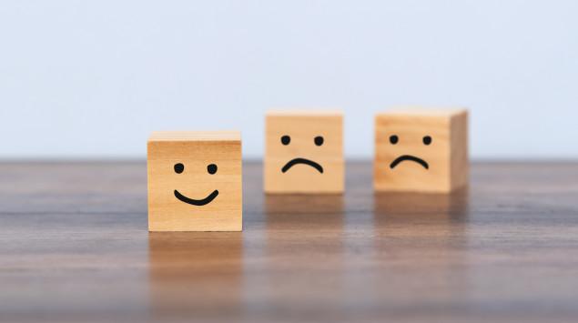 Holzwürfel mit traurigen und fröhlichen Smileys: Bei der Zyklothymia schwankt die Stimmung zwischen Hypomanie und Depression.