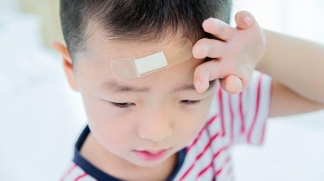 Ein kleiner Junge mit Pflaster auf der Stirn fasst sich an den Kopf.