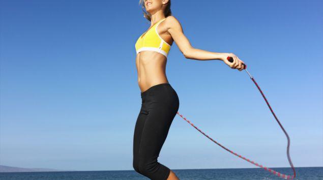 Eine Frau springt Springseil am Strand.