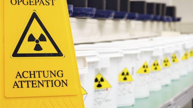Vor einer Reihe Flaschen, die mit dem Strahlenwarnzeichen etikettiert sind, steht ein Warnschild, das ebenfalls vor radioaktiven Stoffen oder ionisierenden Strahlen warnt.