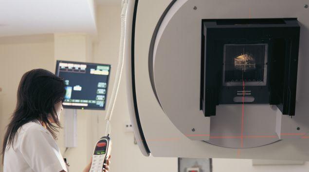 Eine Frau bedient einen Linerabeschleuniger, der zur Strahlenbehandlung von Tumoren zum Einsatz kommt.
