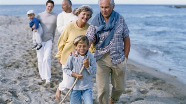 Eine Familie spaziert den Strand entlang.