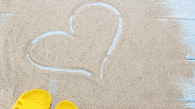 Ein Herz in Sand gemalt, daneben gelbe Badeschuhe.