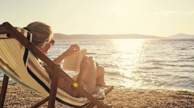 Eine Frau sitzt auf einer Liege am Strand und liest.