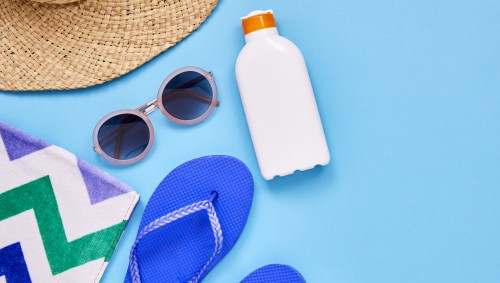 Zusammenstellung von Sonnenhut, Sonnenbrille, Sonnencreme, Sandalen