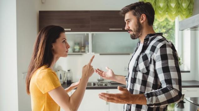 Ein junges Paar steht in der Küche und streitet.